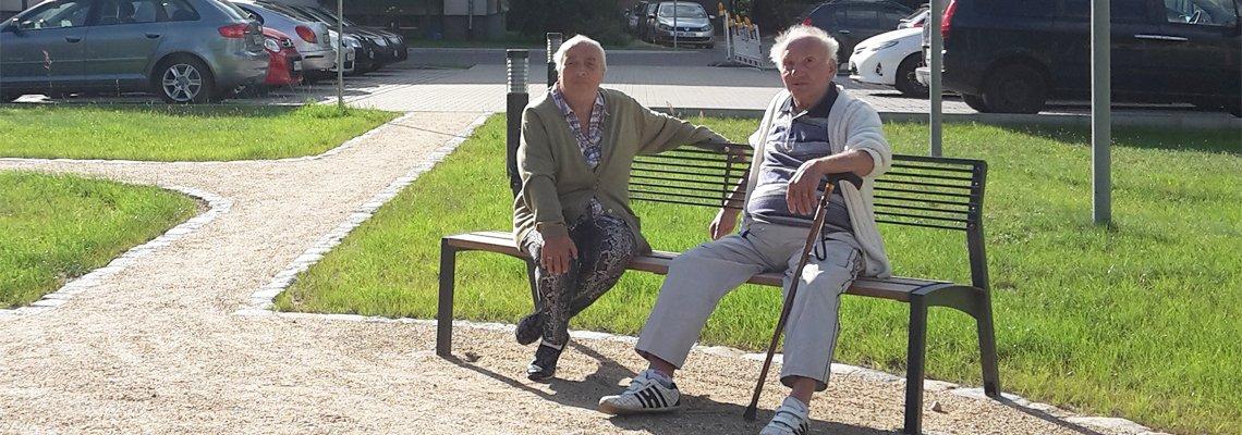Zwei Mieter sitzen auf einer Bank im Wohngebiet der WBG